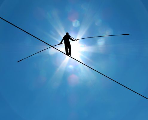 Man silhouetted by the sun and walking across tightrope with balancing pole with a clear sky background