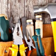 various DIY tools in an orange tool holder secured to a bare wooden wall
