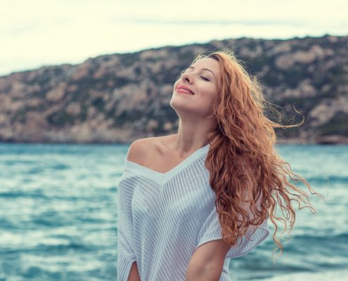 Woman with eyes closed, smiling and taking a deep breath by the ocean