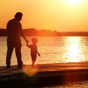 Silhouette of father and son walking on pier holding hands with sun in background